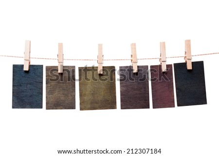 Close up of wooden notes attach to rope with clothes pins on white background