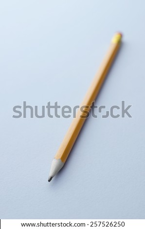 Close up of wooden pencil over blue background - stock photo