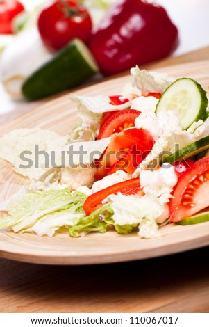 Close up of wooden plate with vegetable salad