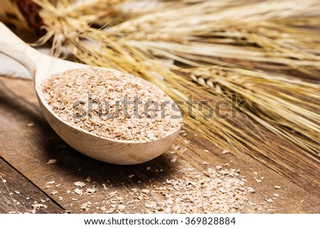 Close-up of wooden spoon filled with wheat bran on the background of wheat ears. Dietary supplement to improve digestion. Source of dietary fiber. Wooden planks background. Shallow depth of field