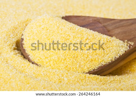 Close up of wooden spoon in raw polenta. - stock photo