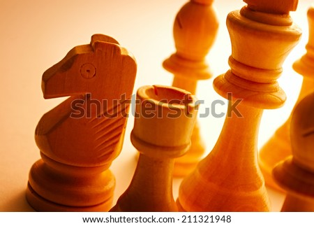 Close-up of wooden vintage chess pieces as knight, pawn, king and bishop - stock photo