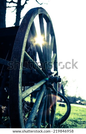 Close up of wooden wheel of an old coach at sunset. Selective focus. Low depth of field. Cross process. Vintage filter. - stock photo
