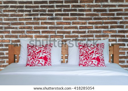 Close up of wooden white bedding sheets and red pillow  on old brick wall - stock photo