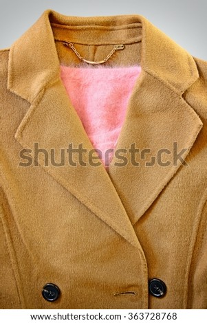 Close-up of wool coat with pink sweater inside. - stock photo
