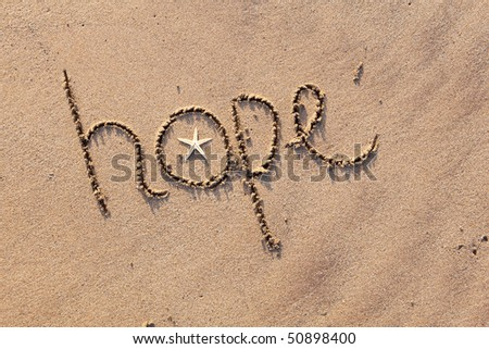 close up  of word 'hope' written in sand at beach