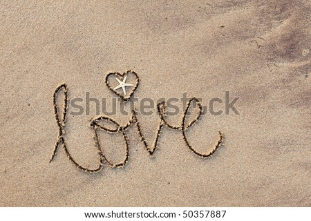 close up of word 'love' written in sand at beach