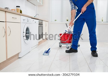 Close-up Of Worker Cleaning Floor With Mop In Kitchen Room - stock photo