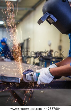 Close Up of Worker cutting metal with grinder in the factory.