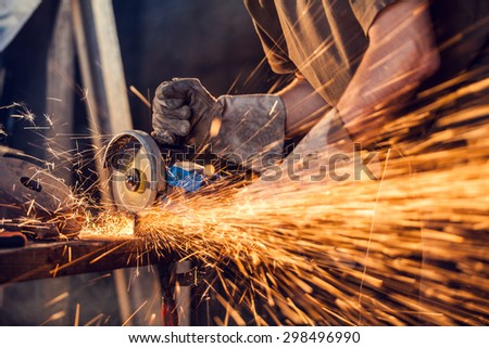 Close-up of worker cutting metal with grinder. Sparks while grinding iron. Low depth of focus - stock photo