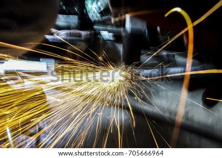 Close-up of worker cutting metal with grinder. Sparks while grinding iron. Low depth of focus. Motion blur. Slow shutter.