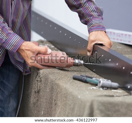 Close up of worker drilling holes in aluminium construction frame with electric drill