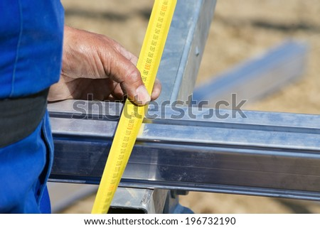 Close up of worker measuring aluminium construction frame with yellow tape - stock photo