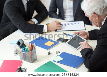 Close-up of working businesspeople sitting at the table - stock photo