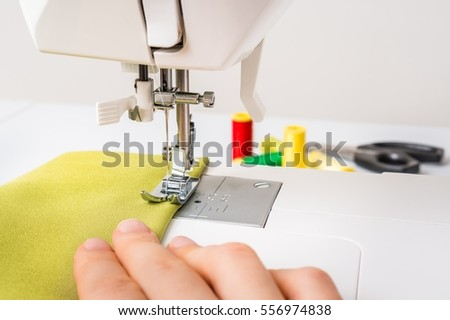 Close-up of working sewing machine foot with green cloth