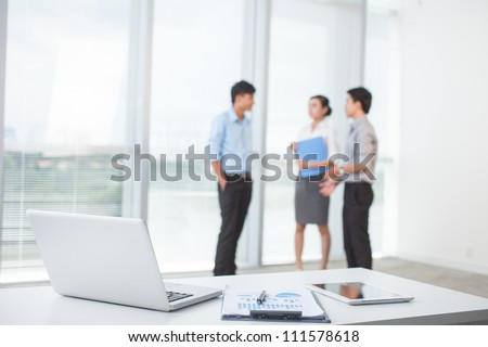 Close-up of workplace in modern office with business people behind - stock photo