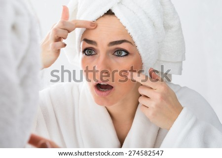 Close-up Of Worried Woman Looking At Pimple On Face In Mirror