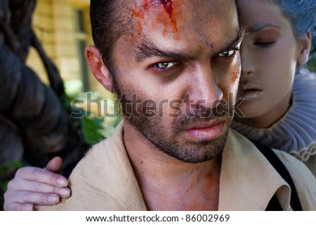 Close-up of wounded male vampire looking at camera, medieval woman embracing him