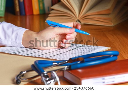 Close-up of writing doctor's hands on a wooden desk. - stock photo