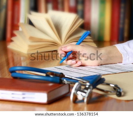 Close-up of writing doctor's hands on a wooden desk - stock photo