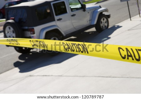 Close up of yellow caution tape with car in the background