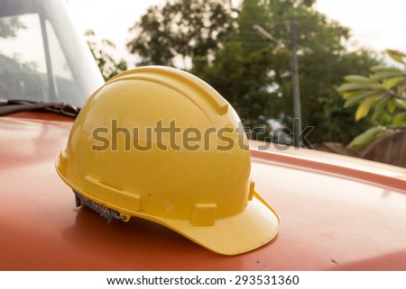Close up of yellow engineer's helmet is placed on the hood of a truck. - stock photo