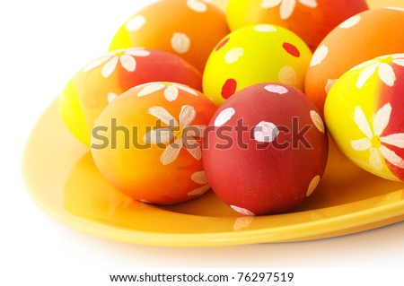 Close-up of yellow, orange and red Easter eggs in orange plate on white background.