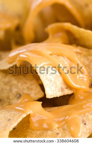 Close-up of yellow tortilla chips covered in nacho cheese - stock photo