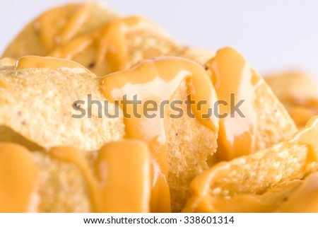 Close-up of yellow tortilla chips covered in nacho cheese on the Grey Background - stock photo