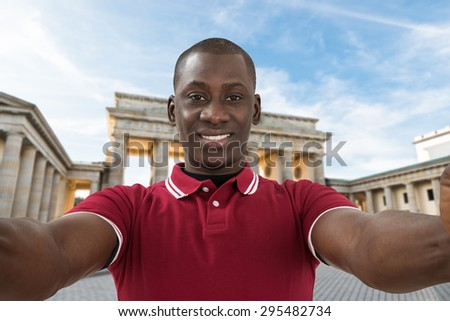 Close-up Of Young African Man Taking Selfie At Brandenburg Gate - stock photo