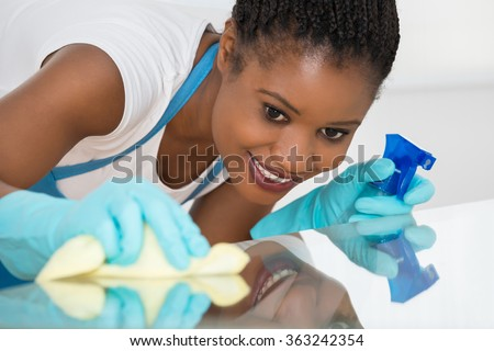 Close-up Of Young African Woman Using Spray To Wipe Glass Desk - stock photo