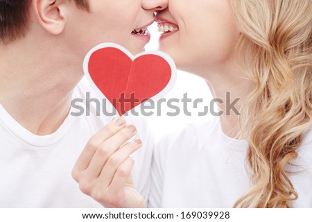 Close-up of young amorous couple touching by their faces while girl holding red paper heart - stock photo