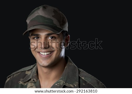 Close-up of young army soldier against black background - stock photo