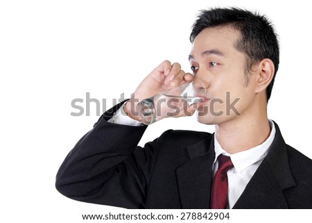 Close up of young Asian businessman drinking a glass of water, isolated on white background