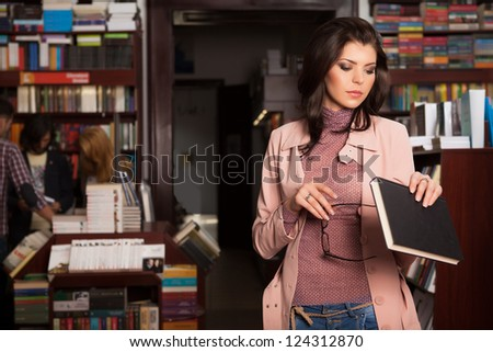 close-up of young attractive caucasian brunette girl in book store elegantly holding i her hands a pair of eyeglasses and a book reading the cover of it - stock photo