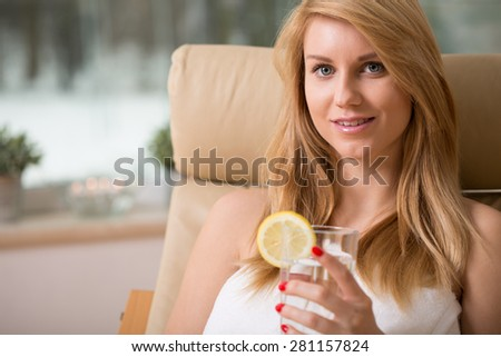 Close-up of young attractive woman drinking water with lemon - stock photo