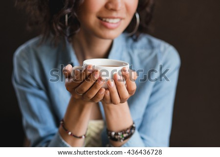 Close up of young beautiful unrecognizable woman hands holding hot cup of coffee or tea with milk