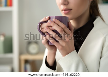 Close up of young beautiful woman hands holding hot cup of coffee or tea. Morning coffee, cold season, office coffee break or coffee lover concept. - stock photo