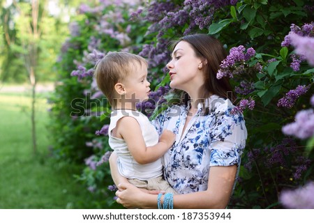 Close up of young beautiful woman with her cute little son. Mother hugs child. Family talking - stock photo