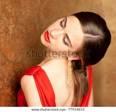close-up of young beautiful woman with red lips and her eyes closed in red dress - stock photo