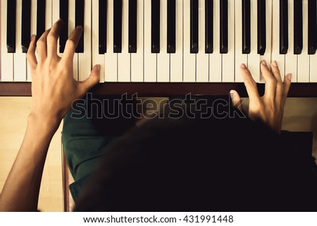 Close up of young boy hands, playing piano. vintage tone filter effected - stock photo