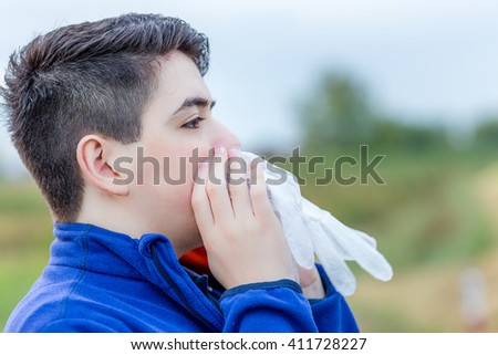 close up of young boy in countryside blowing in a disposable  plastic glove to inflate it
