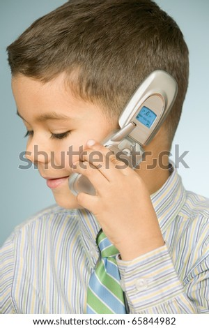 Close up of young boy talking on mobile phone - stock photo