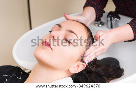Close Up of Young Brunette Woman Lying Back with Eyes Closed and Having Hair Washed by Stylist in Salon Sink - Woman Relaxing While Having Hair Washed