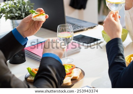Close-up of young businessman eating his sandwiches for lunch - stock photo
