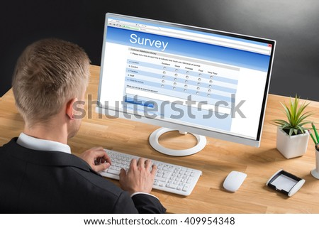Close-up Of Young Businessman Filling Online Survey Form On Computer At Desk - stock photo