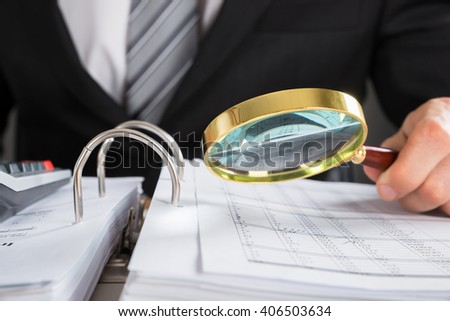 Close-up Of Young Businessman Hand Examining Invoice With Magnifying Glass - stock photo