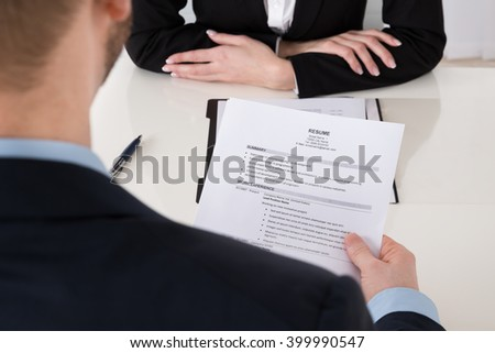 Close-up Of Young Businessman Holding Resume At Office Desk
