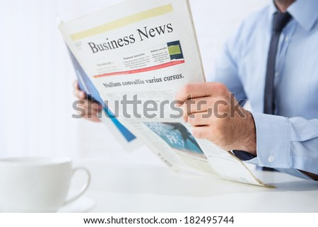 Close up of young businessman reading business news - stock photo