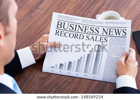 Close-up Of Young Businessman Reading News On Newspaper - stock photo